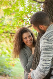 夫妇在秋季森林,偷看从树的后面 图库摄影