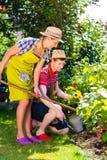 夫妇在种植花的庭院里 免版税库存照片
