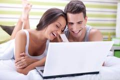 夫妇在网上买与信用卡的床上 库存图片