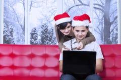 夫妇在网上在圣诞节支付 免版税库存照片