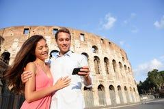 夫妇在罗马使用巧妙的电话的罗马斗兽场 免版税图库摄影