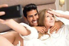 夫妇在获得的床上采取selfie和乐趣,夫妇在拍与智能手机的床上一张照片 库存图片