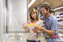 年轻夫妇在超级市场选择冻产品 库存图片
