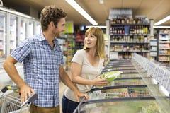 年轻夫妇在超级市场选择冻产品 库存照片