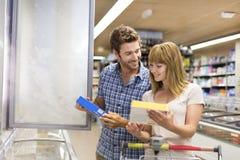 年轻夫妇在超级市场选择冻产品 免版税库存照片