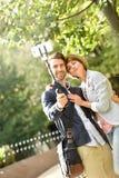 年轻夫妇在采取selfie的公园 免版税库存图片