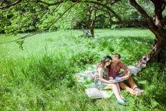 夫妇在野餐放松在绿色公园 库存照片