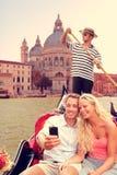 夫妇在长平底船的威尼斯在重创的运河乘坐 库存图片