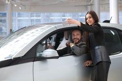 夫妇在陈列室里选择汽车和制造selfie 免版税库存照片