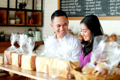 年轻夫妇在面包店商店 免版税库存照片