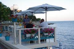 夫妇在餐馆享受一个晚上由海 免版税库存照片