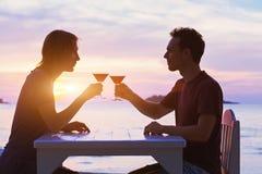 夫妇在餐馆,在海滩的饮用的鸡尾酒 免版税库存照片