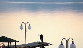 夫妇在马其顿采取selfy在一湖prespa的一个码头 在日落的湖 免版税库存照片