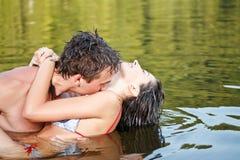 夫妇在水中亲吻 库存照片