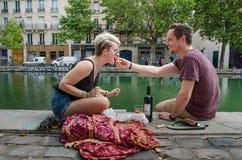 夫妇在巴黎享受在运河圣马丁的银行的午餐 免版税图库摄影