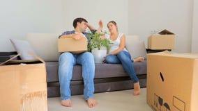 年轻夫妇在移动在他们的新房里和基于是疲乏沙发以后 股票视频