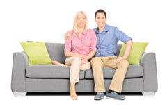 年轻夫妇坐一个现代沙发 免版税库存图片