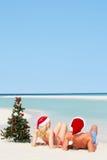 夫妇坐与圣诞树和帽子的海滩 免版税库存图片