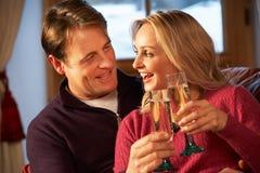 夫妇坐与香宾玻璃的沙发  免版税库存图片