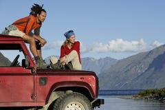 夫妇坐吉普由Mountain湖 免版税图库摄影
