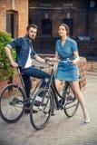 年轻夫妇坐在城市对面的一辆自行车 库存照片