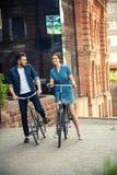 年轻夫妇坐在城市对面的一辆自行车 免版税库存图片