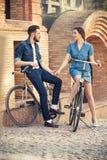 年轻夫妇坐在城市对面的一辆自行车 免版税库存照片