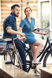年轻夫妇坐在城市对面的一辆自行车 图库摄影