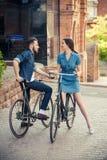 年轻夫妇坐在城市对面的一辆自行车 免版税图库摄影