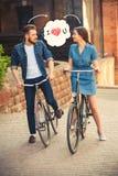 年轻夫妇坐在城市对面的一辆自行车 库存图片