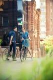 年轻夫妇坐在对面的一辆自行车 库存图片