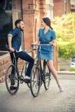 年轻夫妇坐在对面的一辆自行车 免版税图库摄影