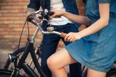 年轻夫妇坐在对面的一辆自行车 库存照片