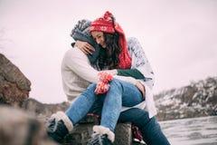 夫妇坐在岩石,拥抱并且微笑着反对积雪的小山和冻湖背景  特写镜头 免版税图库摄影