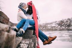 夫妇坐在岩石,拥抱并且微笑着反对积雪的小山和冻湖背景  特写镜头 库存图片