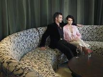 夫妇坐在旅馆大厅的长沙发 免版税库存照片