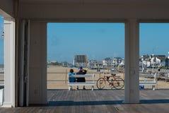 夫妇坐在木板走道的一条长凳 免版税库存照片