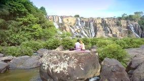 夫妇坐在河急流中的岩石由瀑布 影视素材