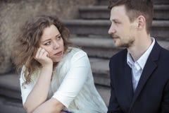 年轻夫妇坐在街道上的台阶 免版税库存照片