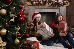 年轻夫妇坐在装饰的fireplac前面的一个地毯 免版税库存图片
