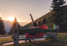 夫妇坐在观看日落和平面飞行的山的长凳 免版税库存照片