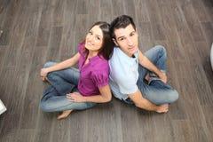 夫妇坐层压制品的地板 免版税库存图片