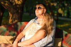 年轻夫妇坐庭院长凳 库存照片