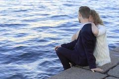 年轻夫妇坐江边 库存照片