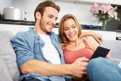 年轻夫妇坐沙发使用数字式片剂 库存图片