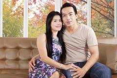 夫妇坐沙发有秋天背景 图库摄影