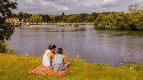 年轻夫妇坐河岸 库存照片