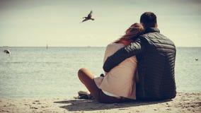 夫妇坐海滩背面图 免版税库存图片