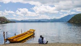 年轻夫妇坐海滩,泸沽湖,丽江,中国 库存照片