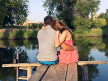 年轻夫妇坐的拥抱在河的桥梁 免版税库存图片